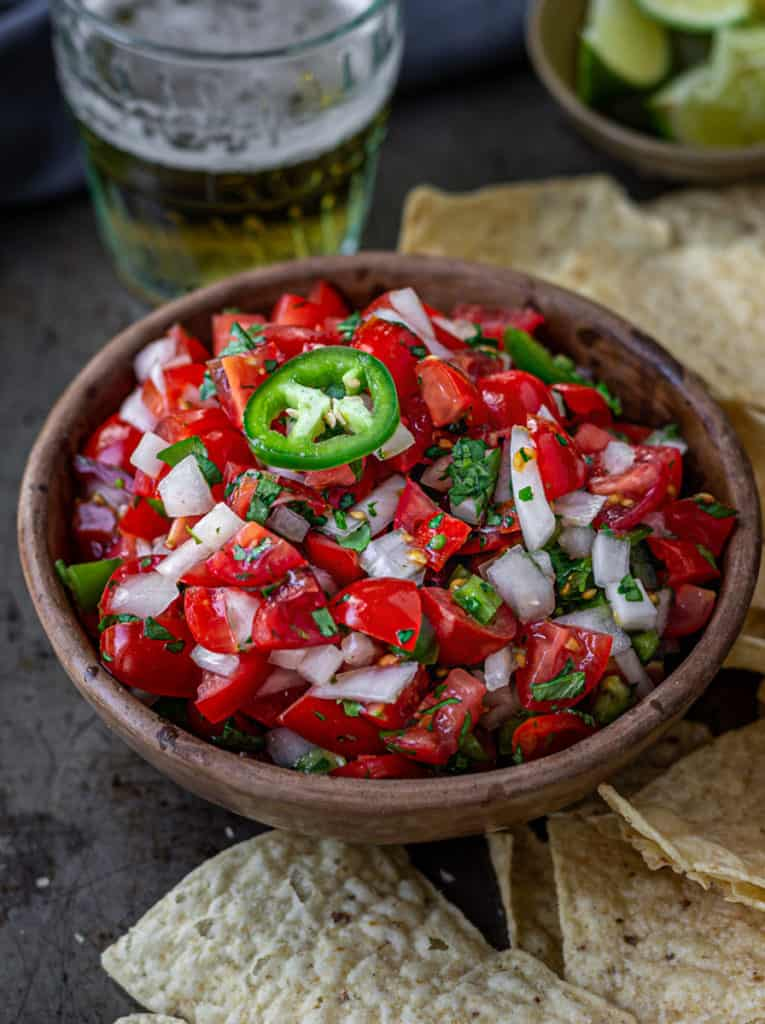 Bowl of pico de gallo on a tray of taco chips.