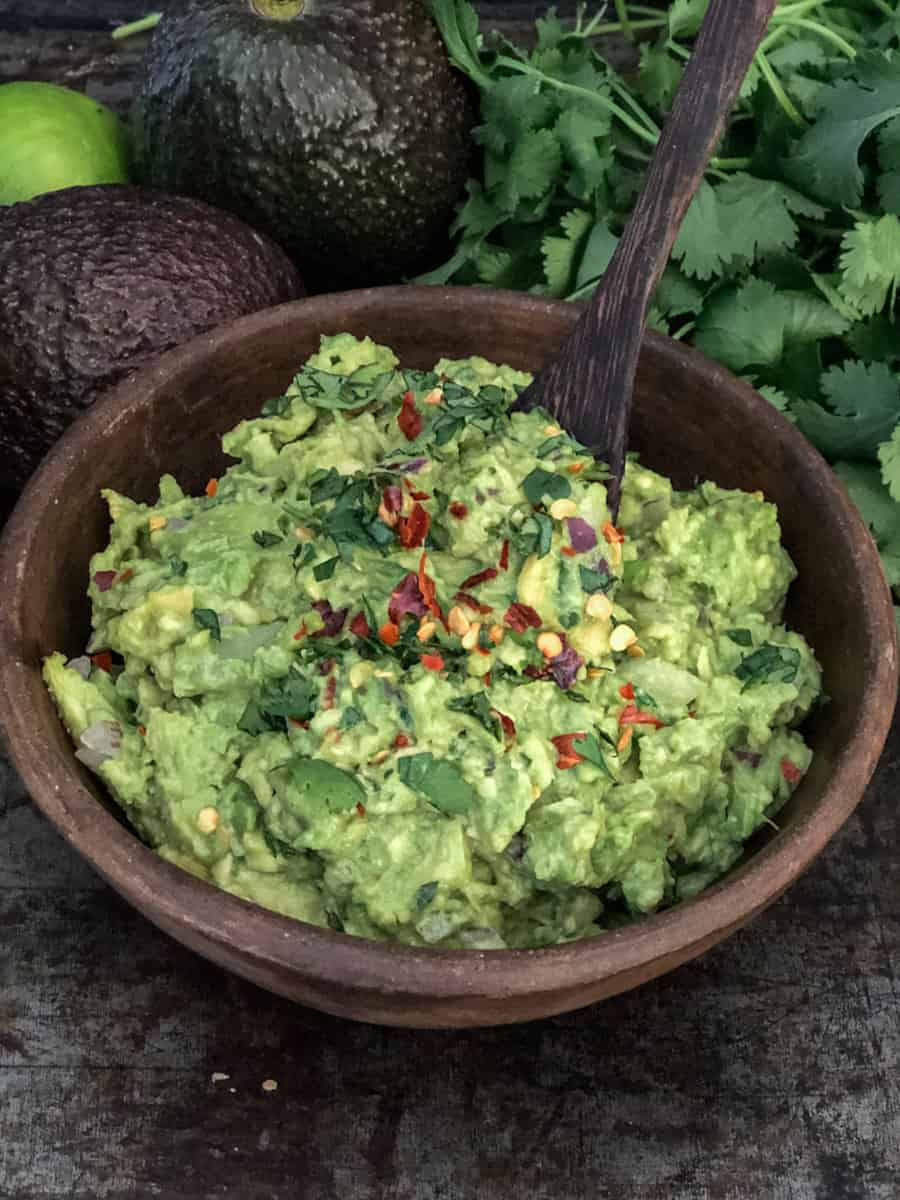 Bowlful of guacamole on a tray with avocados and cilantro.