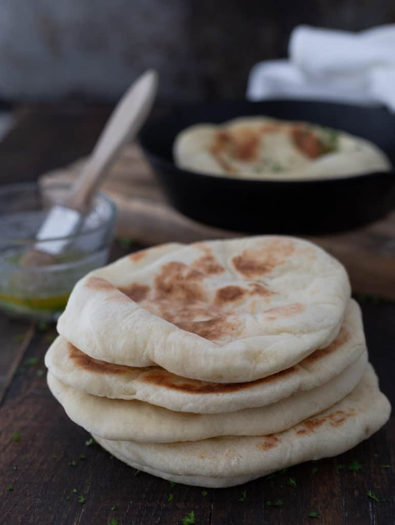 Pile of freshly baked pita pockets in a cast iron pan.