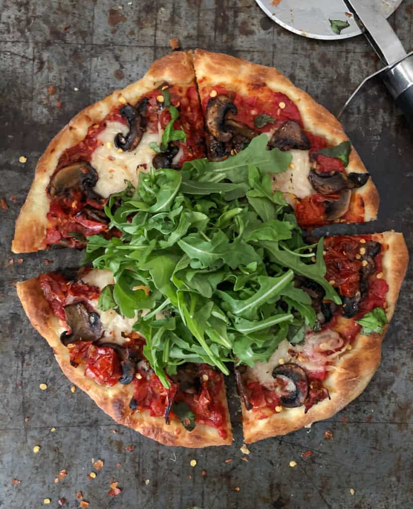 Vegetarian pizza topped with mushrooms, arugula, and tomatoes.