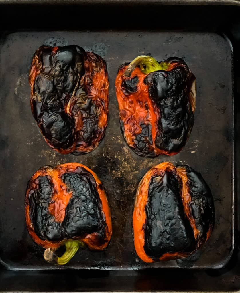 Roasted red peppers charred on a baking sheet.