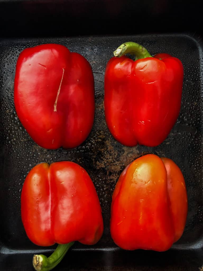 Red peppers cut in half on a baking tray ready for roasting.