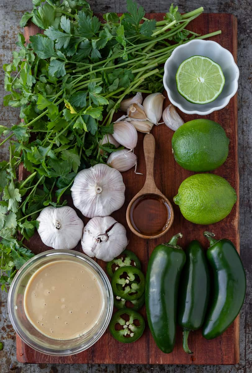 Ingredients for spicy green tahini sauce displayed on a tray.