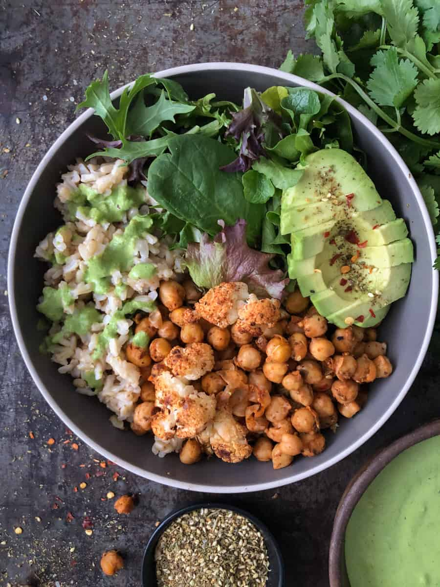 Buddha bowl with cauliflower, chickpeas, avocado and green tahini sauce drizzle.