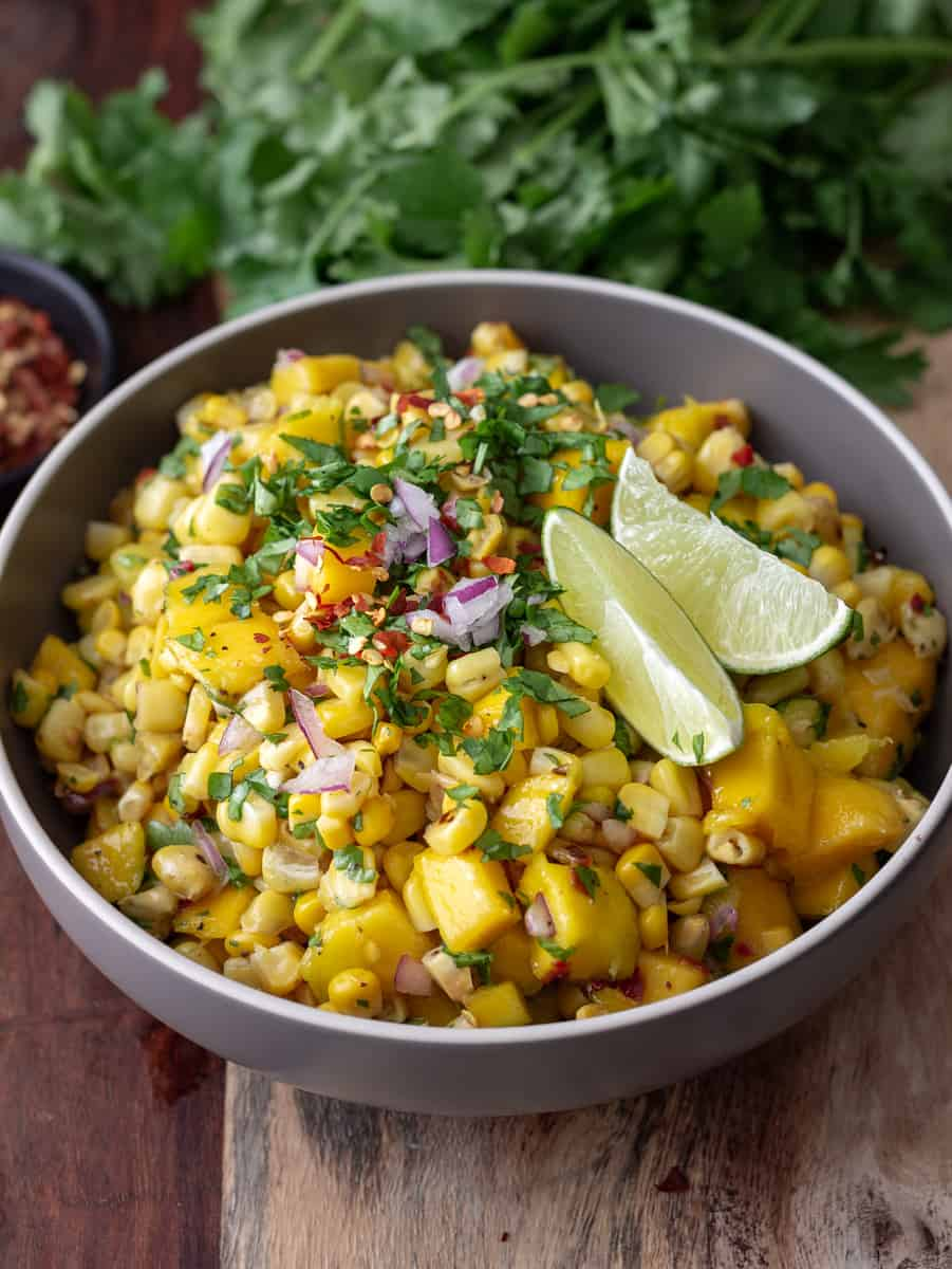 Big bowl of mango corn salsa topped with lime wedges and chopped cilantro.