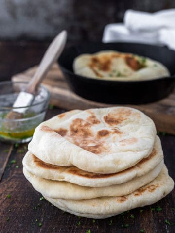 Stack of freshly baked pita bread on board with dish of melted butter and fry pan.