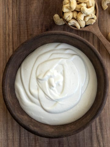 Bowl of cashew cream with spoon of cashew nuts on cutting board.