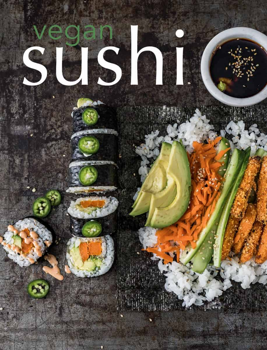 Sushi roll and rice piled high with vegetables on a serving board.