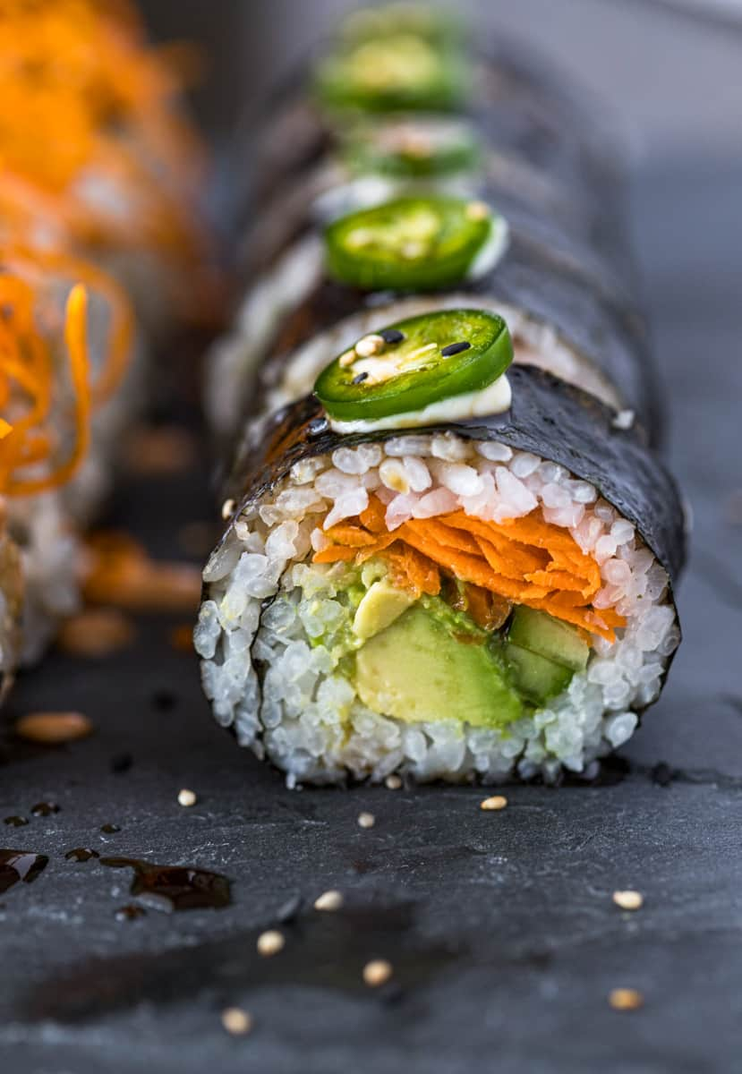 Vegan sushi rolls with avocado and sweet potato on a serving board.