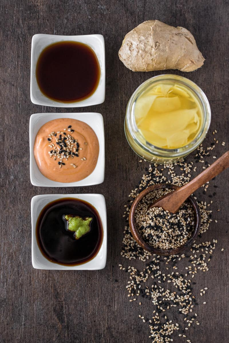 Three bowls of dipping sauce, pickled ginger, and sesame seeds for sushi.