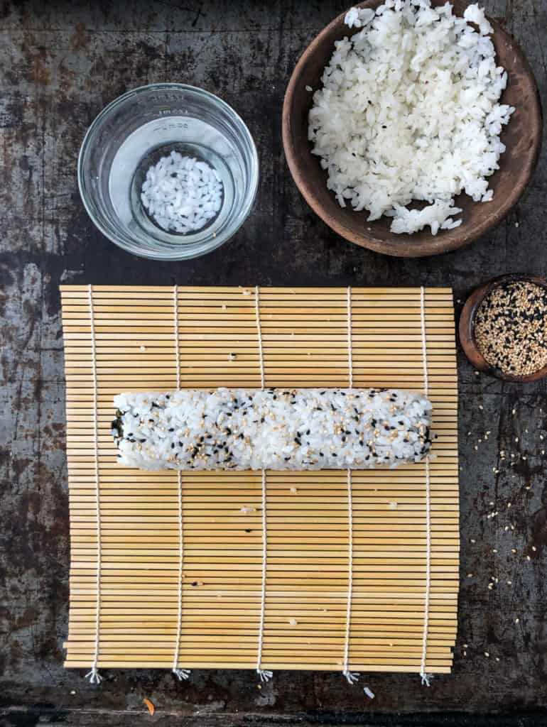 Sushi roll on a bamboo mat with bowls of rice, water, and sesame seeds.