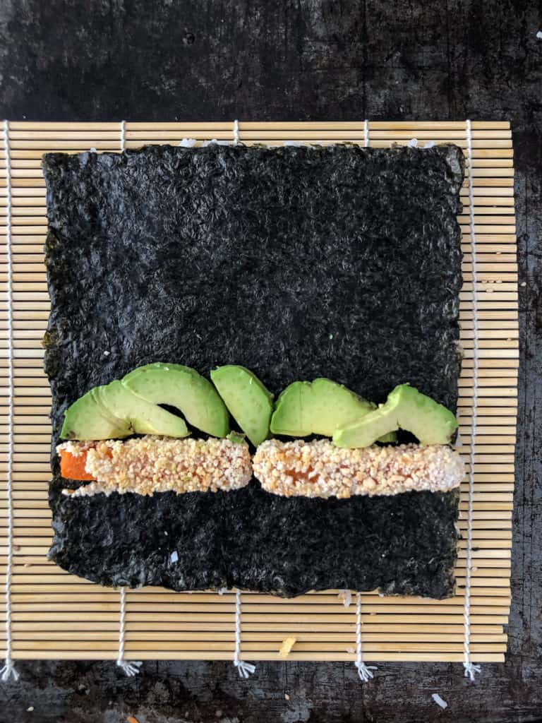 Sushi roll being rolled on a bamboo mat.