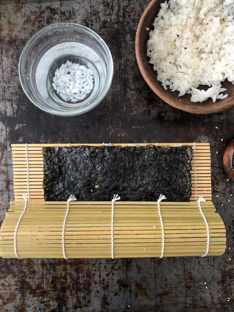 Sushi being rolled in a bamboo mat.