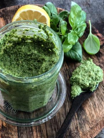 Jar of homemade vegan pesto sauce with basil leaves.