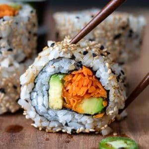 Chopsticks lifting a vegan sushi roll made with carrots and avocado.