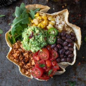 Overhead shot of taco bowl with guacamole, tofu crumble, beans, corn, and tomatoes.