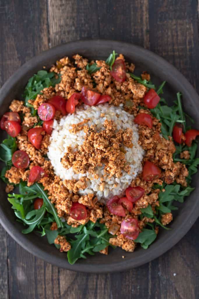 Spicy tofu crumbles on a bed of greens with tomatoes and rice.