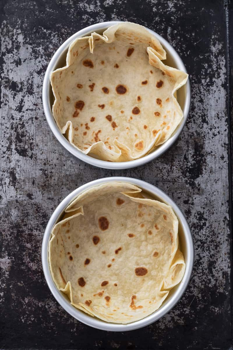 Two tortilla shell bowls on a baking sheet.