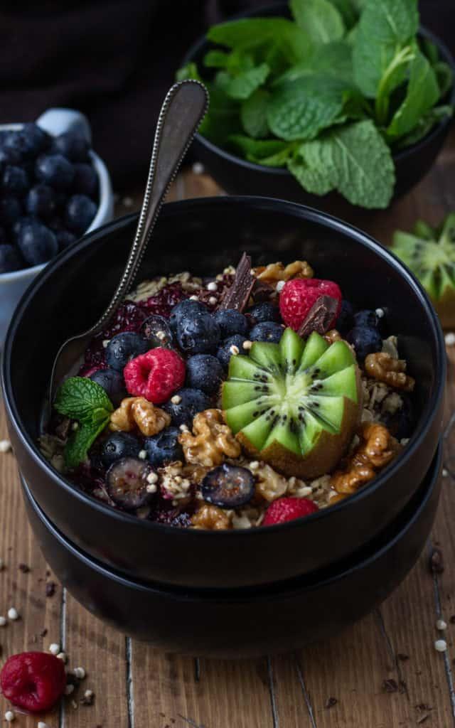 Bowl of porridge topped with fresh berries and kiwi.