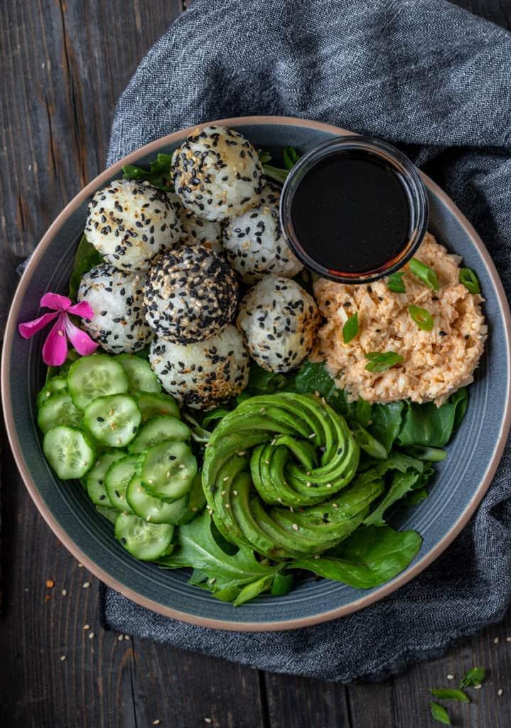 Sushi bowl with spicy vegan crab salad, rice balls and an avocado rose.