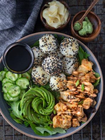 Vegan sushi bowl with tempura mushrooms, rice balls and an avocado rose.
