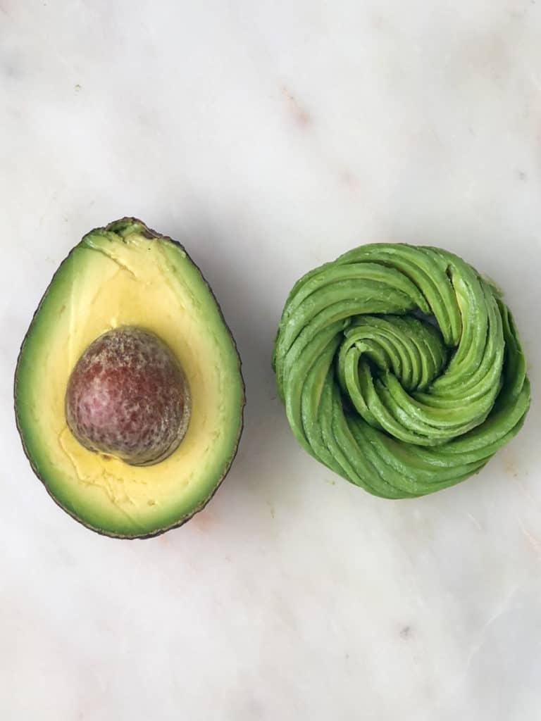 Half an avocado and an avocado rose on a serving tray.
