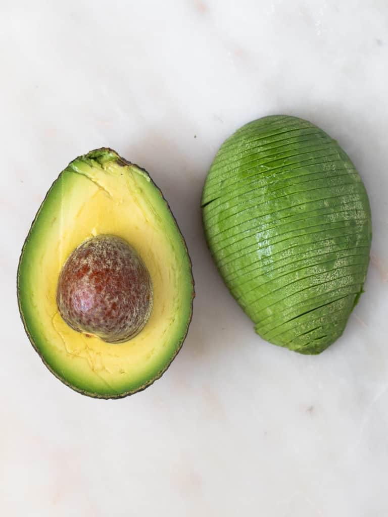 Avocado slice in half sitting on cutting board.