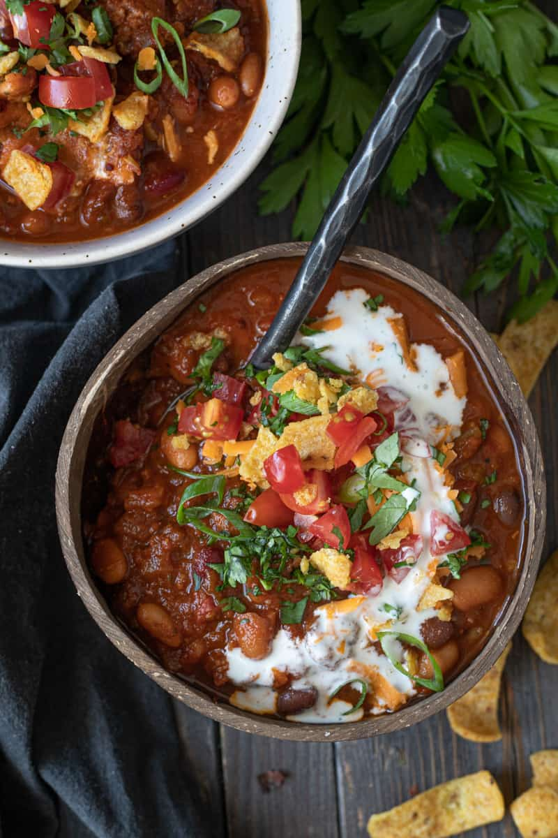 Bowls of vegetarian chili topped with sour cream swirl on serving board.