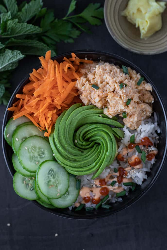 Vegan sushi rice bowl with avocado rose, grated carrots, vegan crab and cucumbers.