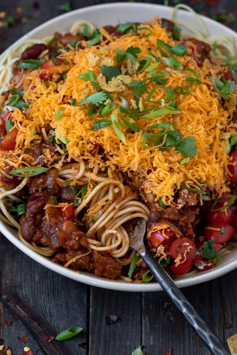 Vegetarian Cincinnati style chili served on pasta with grated cheese.