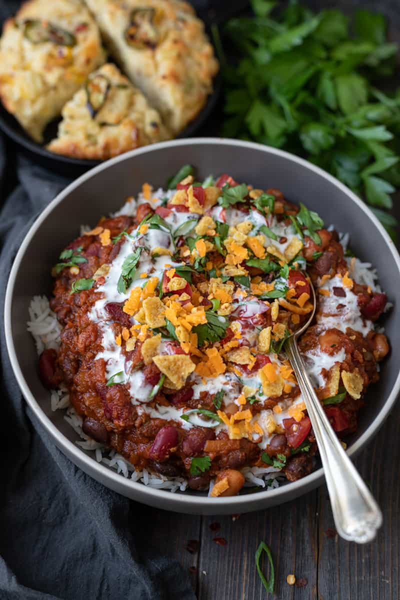 Bowlful of vegetarian chili with a swirl of sour cream and crushed corn chips on top.