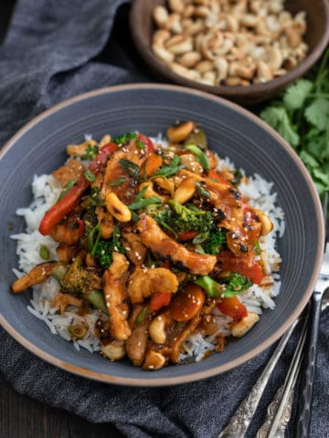 Bowl of vegan cashew chicken made with soy curls brocoli carrots and red peppers on rice.