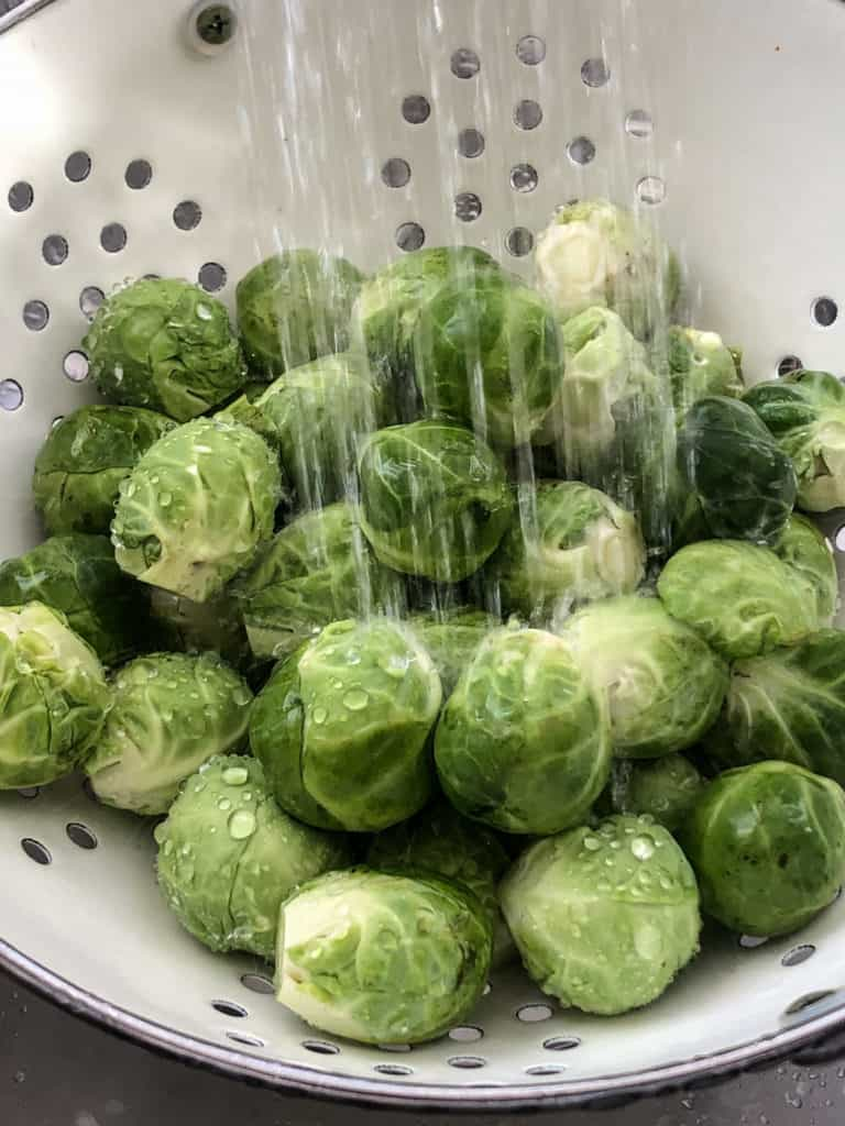 Water showering down on Brussels sprouts in a colander.