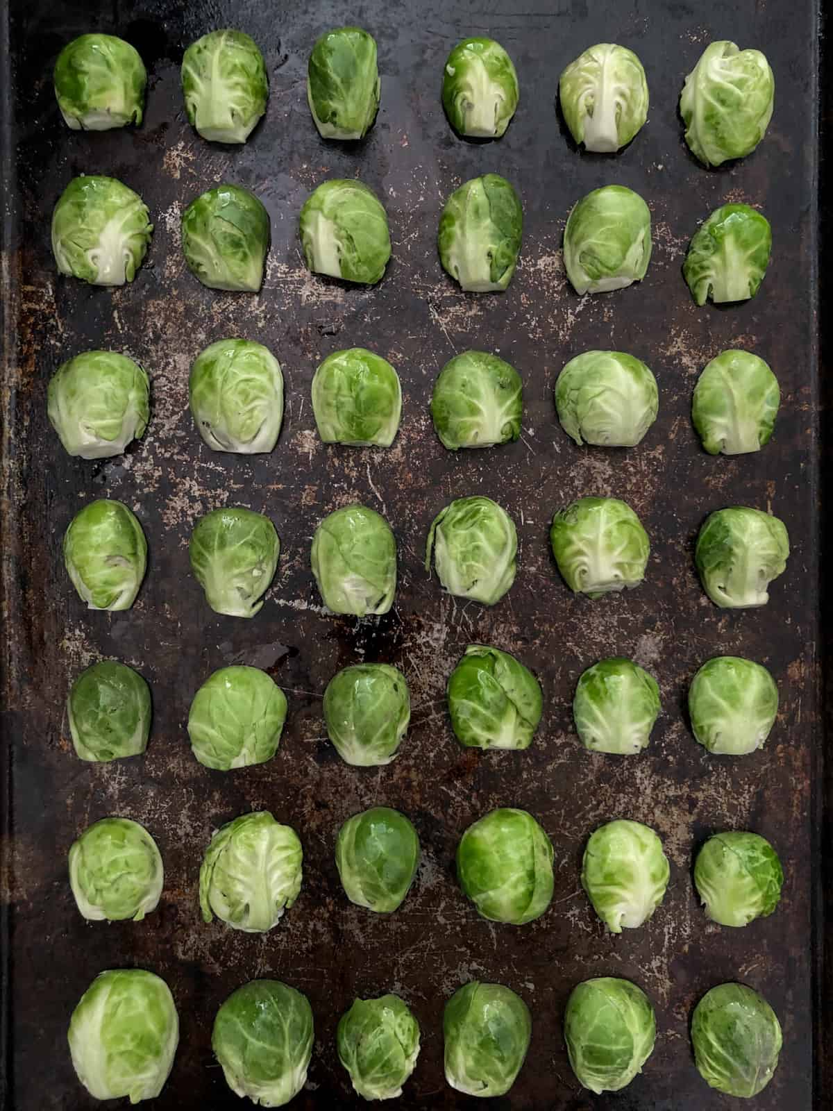 Brussels sprouts halves on a baking sheet.