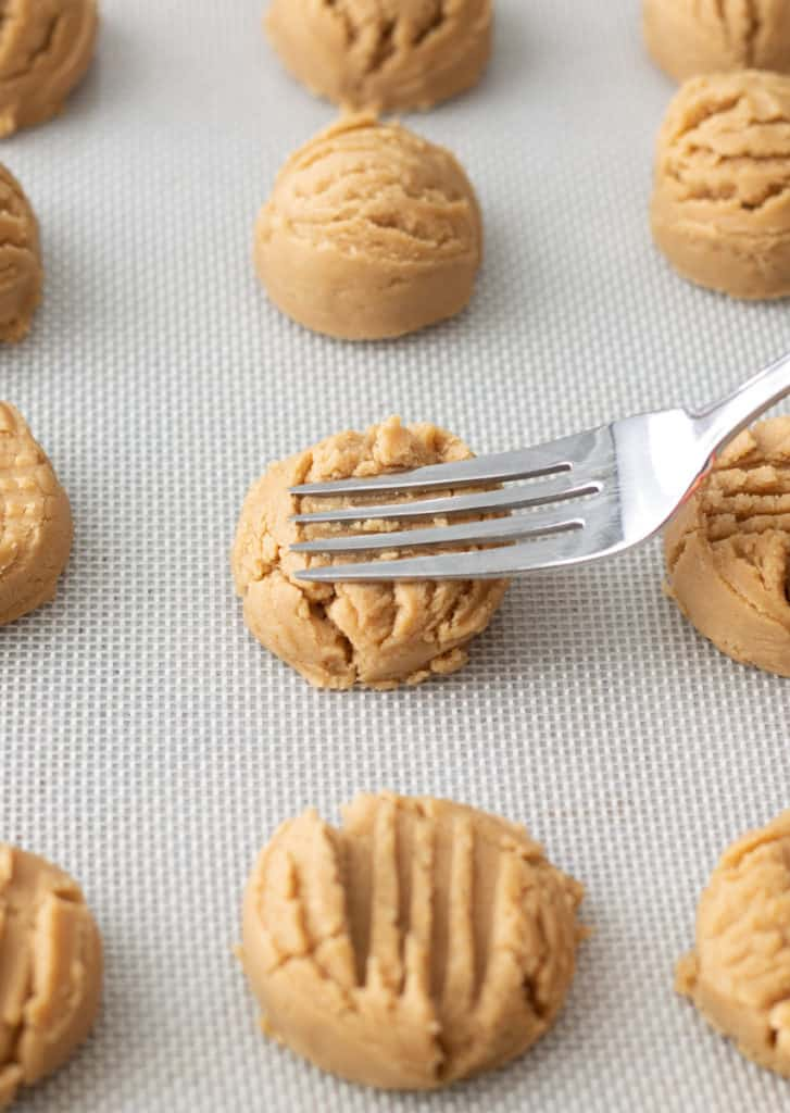 Peanut butter cookie dough balls being pressed with fork.