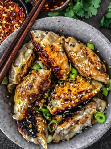 Bowlful of vegetable potstickers with chopsticks and sauce.